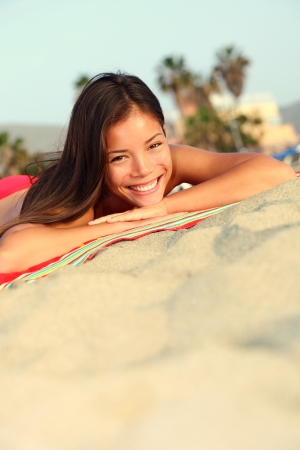 Beach vacation summer woman lying down in sand smiling happy looking at camera  Beautiful young mixed race Caucasian   Asian Chinese girl joyful outside  스톡 콘텐츠
