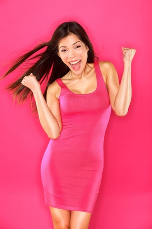 Excited success winner woman portrait on pink background  Young lady celebrating success on pink background  Beautiful smiling happy multiracial Caucasian   Chinese Asian brunette fashion model