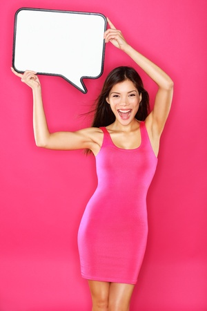 placard: Woman showing sign speech bubble with copy space for text  Beautiful excited smiling happy joyful mixed race Asian   Caucasian female fashion model in pink dress on pink background  Energetic and fresh photo