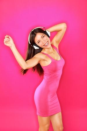 ダンス音楽 mp3 プレーヤーまたはピンク色の背景の美しい幸せな笑顔にピンクの赤いドレスでスマート フォンでセクシーな混合レース アジアのコー
