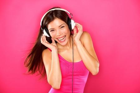 Kopfhörer Musik Frau tanzen, Musik hören über MP3-Player oder Smartphone glücklich energetische Frische multirassischen Asiatisch Chinesisch kaukasischen brünette Tänzerin auf rosa Hintergrund
