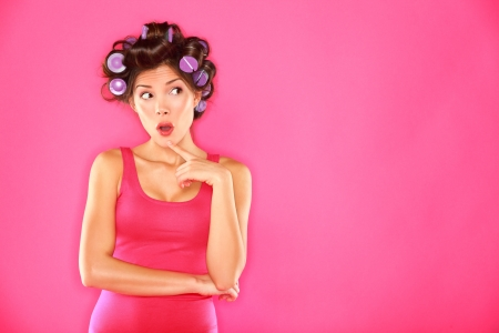 Funny beauty woman with hair rollers looking thinking to the side  Beautiful girl in pink on pink background  Multiracial Caucasian   Asian Chinese female hair model  Фото со стока