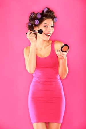 Woman putting makeup getting ready for fun  Funny image of beautiful young female model with hair rollers in pink dress on pink background  Funky trendy young multicultural Caucasian   Asian girl brunette
