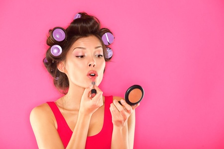 Makeup woman putting lipstick wearing hair rollers getting ready for going out  Funny image of beautiful pretty multiracial girl in pink dress on pink background