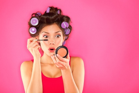 putting up: Makeup mascara woman with hair rollers getting ready looking in pocket mirror  Funny image of beautiful funky trendy young mixed race asian caucasian female fashion model putting makeup on pink background  Mixed race Caucasian   Asian girl