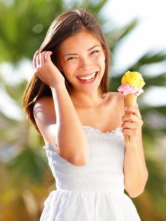 eating ice cream: Ice cream ragazza di mangiare gelato a cono in vacanza estate spiaggia sorridente felice e carina la fotocamera Bella multirazziale Orientale Cinese donna caucasica giovani