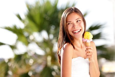 helados: Mujer Helado mirando espacio de la copia feliz, gozoso y alegre lindo multirracial cauc�sica china asi�tica modelo de mujer joven que come el cono de helado en la playa del verano