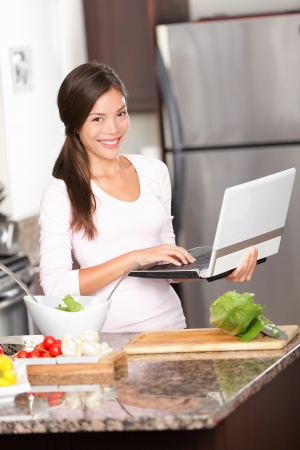 Kitchen woman on laptop PC cooking making food using computer for recipes etc  Beautiful young modern lifestyle image of multiracial Caucasian   Chinese asian young woman at home  photo