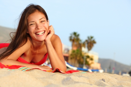 girl with towel: Happy beach girl laughing smiling lying down enjoying sunshine on summer vacation  Gorgeous beautiful young mixed race Caucasian   Asian Chinese woman having fun  Stock Photo