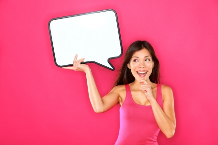 Woman showing sign speech bubble banner looking happy excited on pink background  Beautiful young multiracial Caucasian   Asian Chinese joyful model on pink background having idea