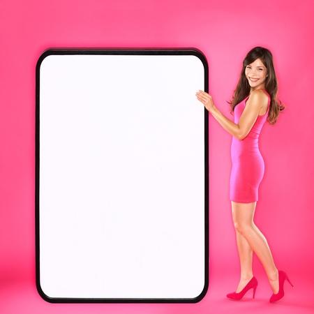 Frau zeigt großes Schild Schöne gerne sexy junge Frau im rosa Kleid mit großen leeren leeren Schild mit Kopie Platz für Ihren Text oder Design Mixed Rennen asiatischen kaukasischen Frauen Mode-Modell auf rosa Hintergrund