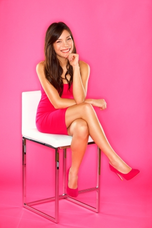 sitting on: Women sitting portrait on pink  Woman sitting on chair in full length studio portrait on pink background  Beautiful smiling happy Asian Chinese   Caucasian