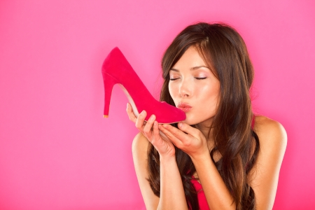Woman kissing shoe  Women loves shoes concept  Multiracial girl and pink high heels shoes on pink background  Beautiful young happy mixed race Asian Chinese and Caucasian female model  photo