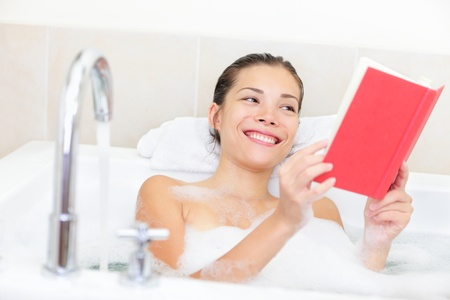 woman in bath: Woman reading book in bath relaxing smiling happy in bathtub full of soap foam  Relaxed beautiful young mixed race  Asian   Caucasian  female model in bathroom at home  Stock Photo