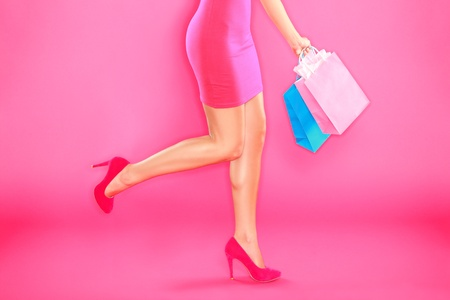 shoe model: Pink shopping. Woman shopper legs, high heels and shopping bags on pink background. Stock Photo