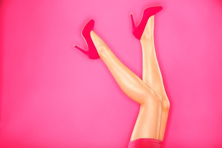 Woman fashion pink high heels and sexy legs. Hot pink high heels shoes and sexy female legs on pink background. photo