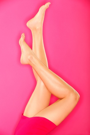 Sexy legs skin care. Woman showing beautiful female legs and bare feet on pink background. photo