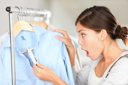 Compras mujer sorprendida en precio. La mujer compradora divertido mirando sorprendido por el precio. Mestizos de raza caucásica / asiática china joven modelo femenino en la tienda de ropa.