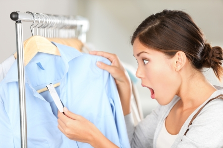 Shopping woman shocked over price tag. Funny shopper woman staring amazed at price. Mixed race Caucasian / Asian Chinese young female model in clothing shop. Standard-Bild