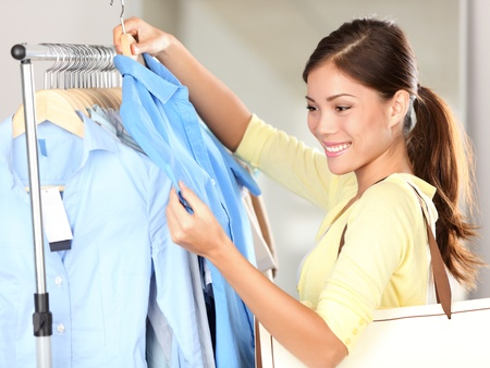 clothing rack: Woman shopping in clothing store looking at clothes smiling happy. Mixed race Asian Chinese  Caucasian young casual woman shopper.