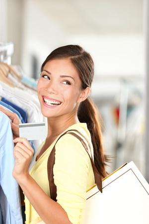 Einkaufen Frau zeigt Kreditkarte glücklich lächelnde Innen in Bekleidungsgeschäft. Junge schöne multi-ethnischen Caucasain  chinesische asiatische Frau Shopper.