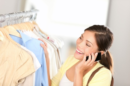 Shopping woman talking on phone joyful and happy shopping for clothes inside in clothing shop. Beautiful young multiethnic Asian Chinese / Caucasian female shopper. Stock Photo - 13448685