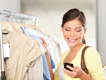 mobile app: Modern woman shopping looking at smartphone texting or talking smiling happy in clothes store. Beautiful young mixed race Asian  Caucasian young woman shopper. Stock Photo