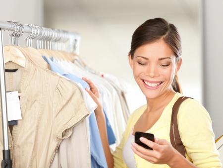 Moderne Frau beim Einkaufen Blick auf Smartphone SMS oder Sprechen lächelt glücklich in Bekleidungsgeschäft. Schöne junge gemischte Abstammung Asian  kaukasischen jungen Frau Shopper.