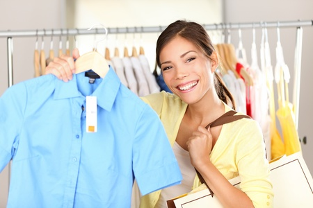 Woman shopping clothes showing shirt in clothing store smiling happy looking at camera. Beutiful young mixed race Asian Chinese  Caucasian young woman shopper. photo