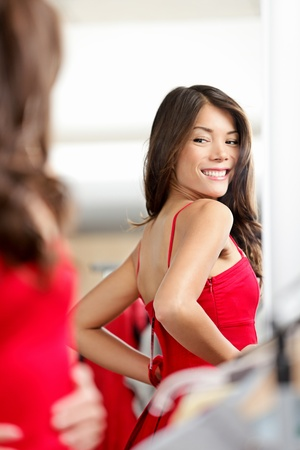 Woman trying clothes  red dress in clothing store changing room looking at mirror smilng happy. Beautiful young multiethnic girl in clothing store.