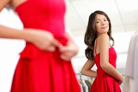 fitting: Girl trying dress in looking in mirror cheerful and happy. Cute beautiful mixed race Asian  Caucasian young woman oin red dress.