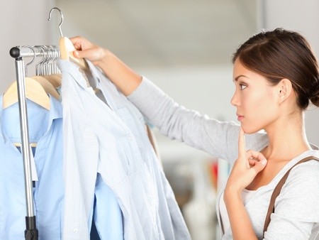 Shopper woman choosing clothes thinking looking at clothing while shopping in store. Beautiful young multiracial Caucasian Asian young woman model.