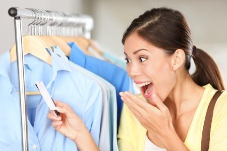 Shopper Frau über Verkaufspreis überrascht. Alles Gute zum asiatischen Einkaufs-Frau über Rabatt Preise überrascht Blick auf Preisschild auf der Kleidung. Mixed Rennen Asiatisch Chinesisch  Kaukasischen jungen weiblichen Modells.