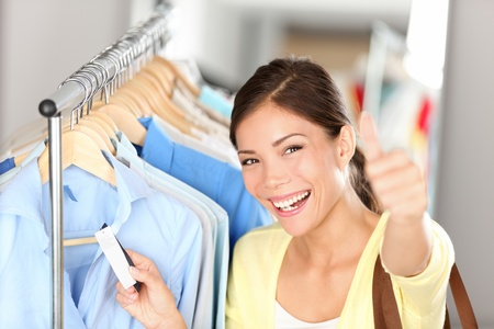 Happy shopping woman showing thumbs up while holding price tag on clothes on clothing rack. Beautiful joyful smiling multiethnic Asian Chinese  Caucasian young female shopper. photo