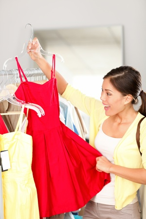 Woman shopping buying clothing holding red dress smiling happy and excited during sale in clothing store. Beautiful young multi-ethnic Caucasian / Asian Chinese woman shopper.
