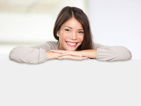 sale shop: Asian sign woman happy showing blank empty billboard sign leaning causual and relaxed smiling content. Multiethnic woman model of mixed race Asian and Caucasian ethnicty. Stock Photo