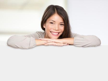 Asiatische Zeichen Frau glücklich zeigt leere leere Plakatwand Schild gelehnt causual und entspannt lächelnd Inhalt. Multiethnischen Frau Modell der gemischten Rennen asiatischen und kaukasischen ethnicty.
