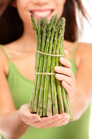 Asparagus  woman holding showing asparagus in closeup  Healthy eating concept
