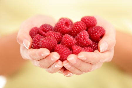 handful: Raspberries  Woman showing raspberries in closeup  Healthy food and raspberry concept