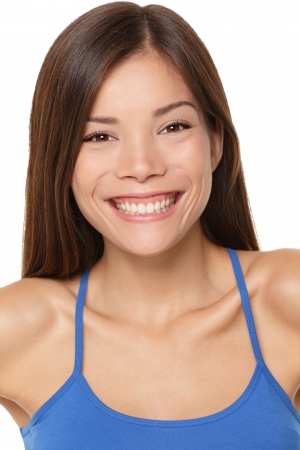Multicultural woman smiling happy portrait closeup isolated on white background. Beautiful young mixed race Caucasian / Chinese Asian female model in her twenties. Stock Photo