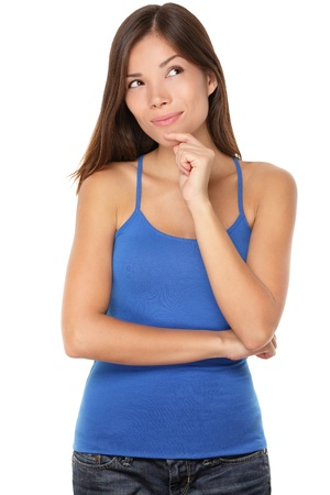ponder: Thinking young woman looking at copy space. Beautiful pensive mixed race Caucasian  Chinese Asian girl isolated on white background in blue tank top. Stock Photo