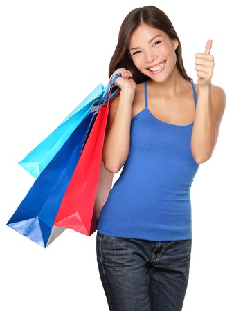Shopping woman showing thumbs up success holding shopping bags isolated on white background. Beautiful young mixed race Asian Caucasian female shopper. Stockfoto