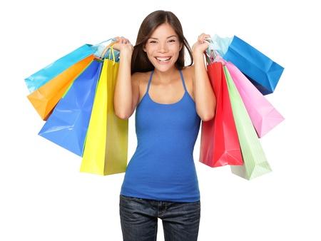 Shopper vrouw met boodschappentassen. Jonge mooie vrouw tijdens het winkelen verkoop houdt vele kleurrijke boodschappentassen geïsoleerd op witte achtergrond in de studio. Pretty multiraciale Aziatische Chinese  Kaukasische vrouwelijke model. Stockfoto