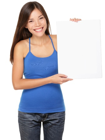 Sign woman holding showing white blank paper placard. Smiling happy young asian girl in tank top isolated on white background in studio. photo