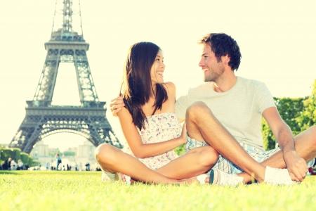 Viajes pareja de turistas en la Torre Eiffel de París sonriente feliz durante el viaje de París de viaje. Hermosa pareja interracial alegre joven sentado en Champ de Mars se divierten. Estilo vintage retro procesado.