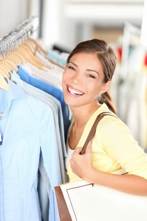의류 매장에서 옷을 쇼핑 행복 구매자 여자 즐거운 smilng 카메라를 찾고. 혼합 된 경주 아시아 중국  백인 젊은 여자.
