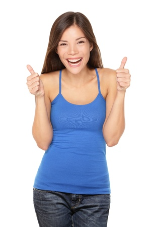 Happy woman giving thumbs up success hand sign smiling joyful and happy. Pretty young multiracial Asian / Caucasian female model in tank top isolated on white background in studio.