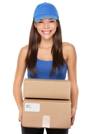Bezorger deelneming pakketten dragen blauwe dop. Vrouw koerier glimlachend gelukkig geïsoleerd op witte achtergrond. Mooie jonge gemengd ras Kaukasische  Chinese Aziatische vrouwelijke professionele.