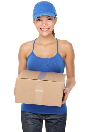 Levering per post vrouw met en het leveren van pakket dragen blauwe dop. Vrouw koerier glimlachend gelukkig geïsoleerd op witte achtergrond. Mooie jonge gemengd ras Kaukasische  Chinese Aziatische vrouwelijke professionele. Stockfoto