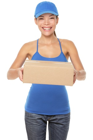 Female package delivery person giving packages wearing blue uniform. Woman courier smiling happy isolated on white background. Beautiful young mixed race Caucasian / Chinese Asian female professional courier.